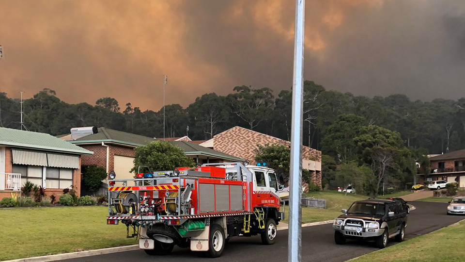 Bushfire survivors in Australia huddle on beach to escape blaze