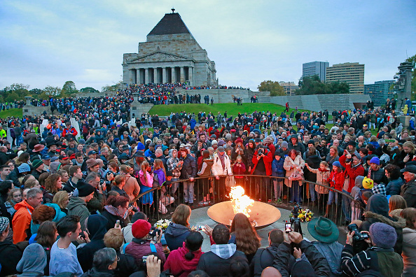 Crowds gathering around the eternal flame at the dawn service on Anzac Day at the Shrine of Remembrance.