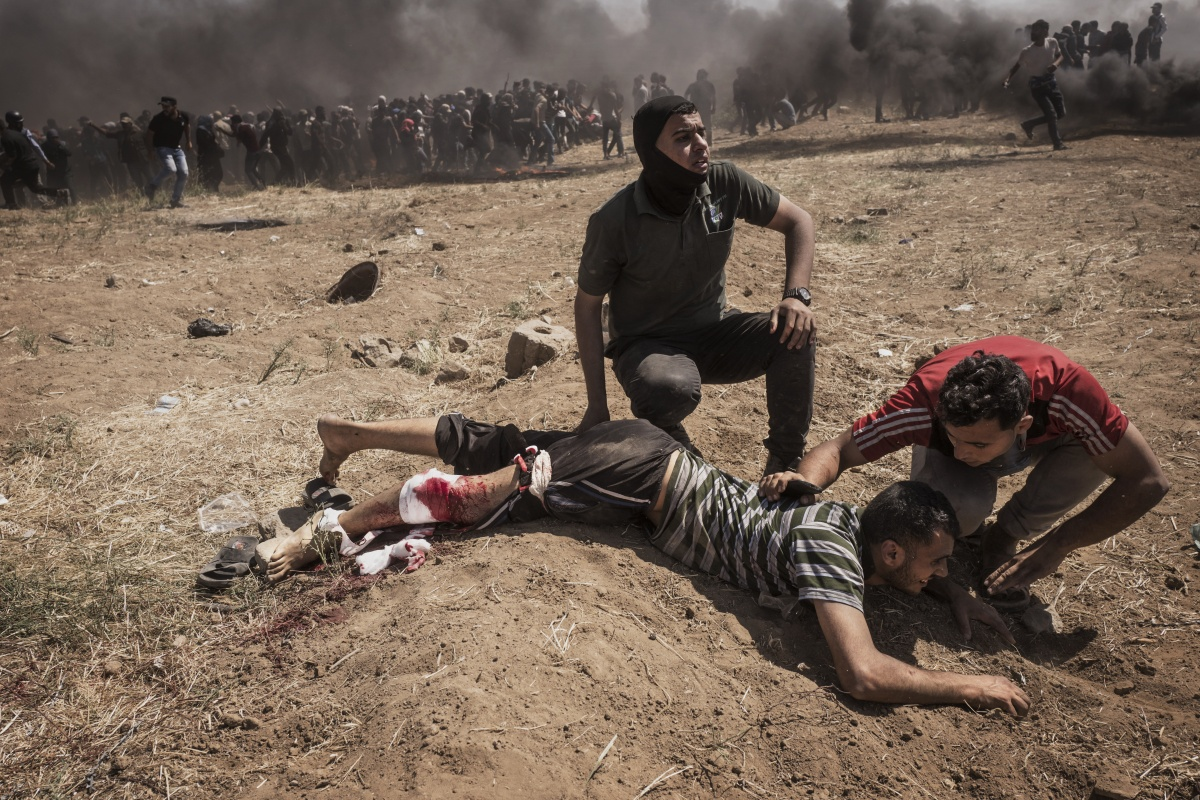 Men assist a wounded Palestinian during clashes on the Gaza border on Monday