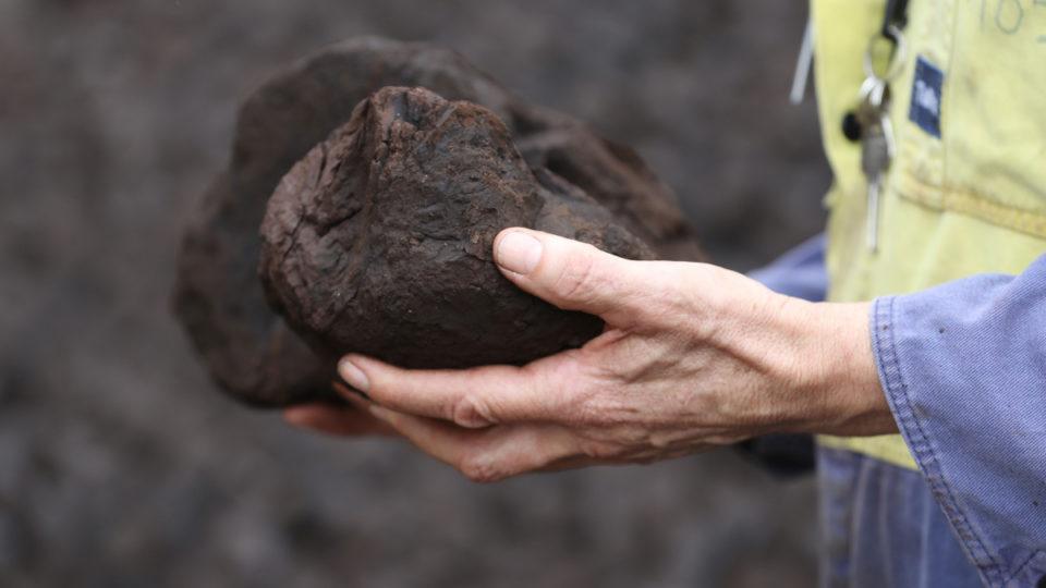I miner handling a lump of coal.