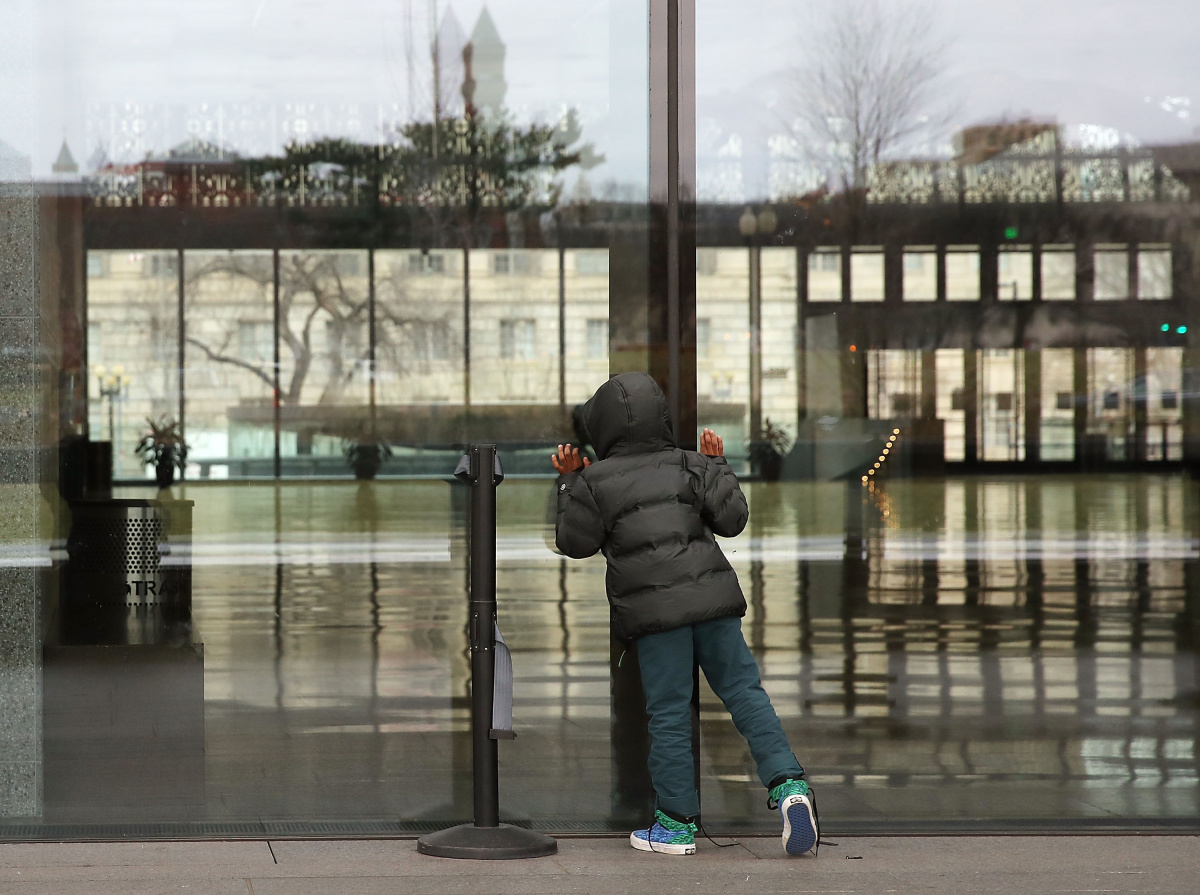 A boy peers into a closed and deserted Smithsonian museum.