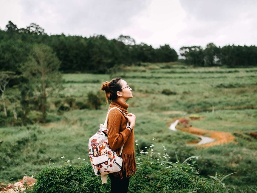A young woman standing in a field.