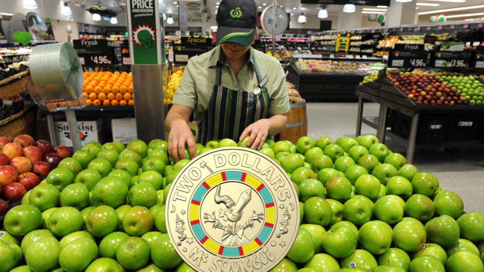 A Woolworths employee sorts apples with a coin superimposed on top.