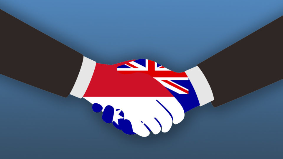 Hands representing Australia and Indonesia shake.