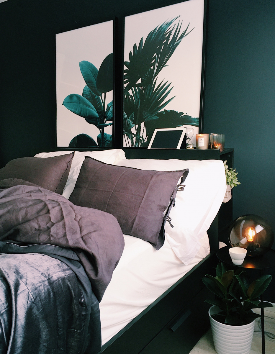 A bedroom with deep green wall