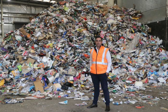 AWMA chief executive Adam Faulkner in front of a huge pile of recycling.