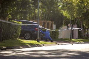 PHOTO: A forensic officer collected evidence from the scene, at Delfin Drive, MacGregor, on Monday. (ABC News: Tim Swanston)