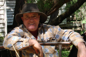 A smiling middle-aged farmer in a hat leans on a gate