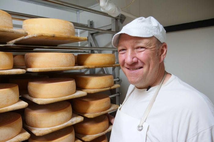 A smiling man in white overalls stands beside several wheels of cheese at a factory