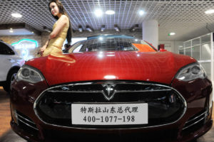 A model poses with a Tesla Model S.