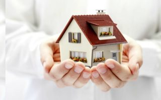 A small house being held in a business person's hands.