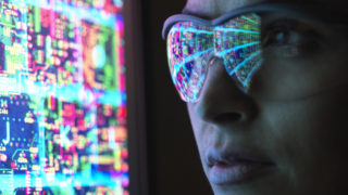 Electronic circuit board on computer monitor reflecting in glasses of a female engineer