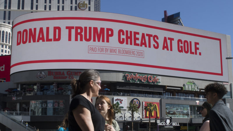 People walk past a billboard paid for by Democratic presidential hopeful Mike Bloomberg, that is attacking President Trump and is displayed on the iconic Las Vegas Strip, in Nevada, on February 21, 2020. Photo: Getty