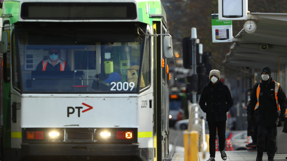 MELBOURNE, AUSTRALIA - JULY 23: People are seen at a tram stop on July 23, 2020 in Melbourne, Australia. Face masks or face coverings are now mandatory for anyone leaving their homes in the Melbourne metropolitan area or the Mitchell Shire. Under the new rule, which came into effect at midnight on Thursday, anyone failing to wear a mask in public can receive a $200 fine. Metropolitan Melbourne and the Mitchell shire remain in lockdown due to the rise in COVID-19 cases through community transmissions, with residents in lockdown areas under stay at home orders until 19 August. People are only able to leave home have for exercise or work, to buy essential items including food or to access childcare and healthcare.