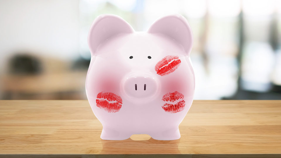 A piggy bank with kiss-shaped lipstick marks all over.