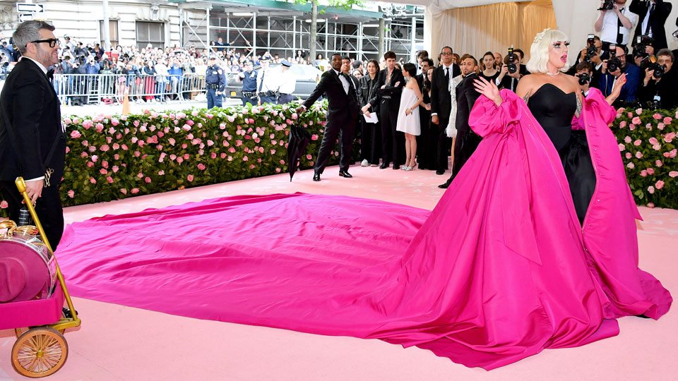 Lady Gaga in giant hot pink wrap on Met Gala pink carpet, with male attendents