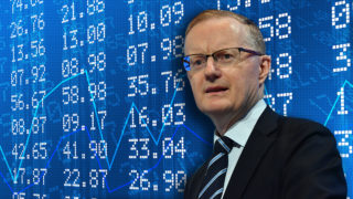 Philip Lowe stands in front a screen of financial data.