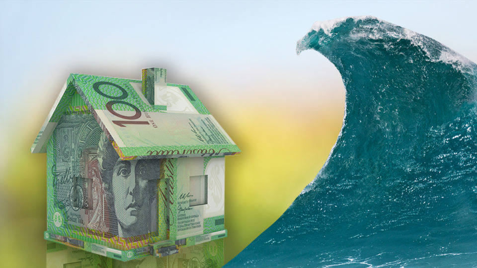 A house made of money about to be wiped out by a huge wave.