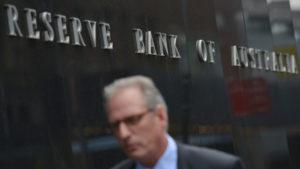A man walks past the Reserve Bank of Australia.