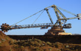 A mining reclaimer shifts iron ore from a stockpile to a conveyor belt in Western Australia.