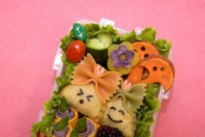 Two pastries with seaweed faces sitting in a lunchbox with vegetables cut into shapes.