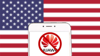 A Huawei phone with a logo on the screen that's been crossed out, all superimposed on the US flag.