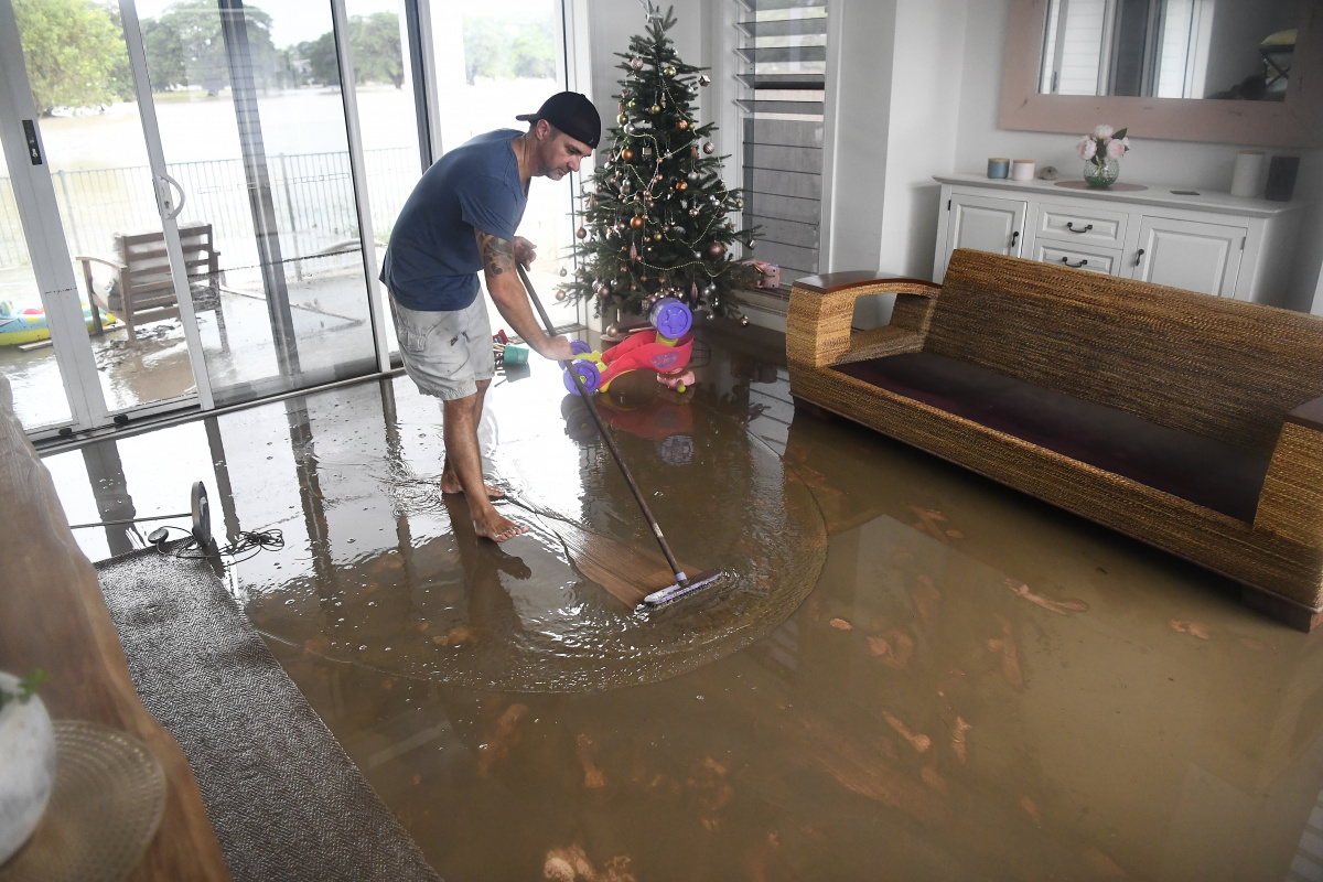 Townsville resident David Mitchell sweeps out his muddy loungeroom after the 2019 flood.
