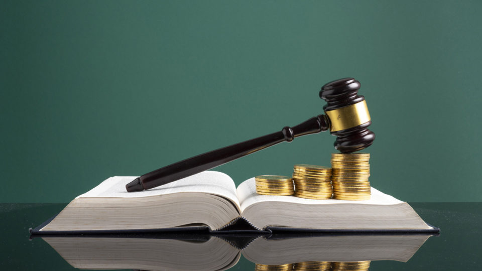 A law book and gavel covered in coins.