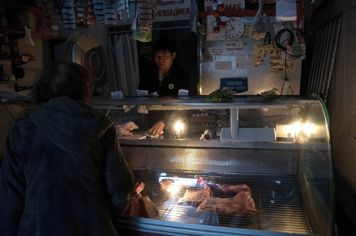A butcher in Buenos Aires uses battery powered lights to keep his shop open during the massive blackout. Photo Getty