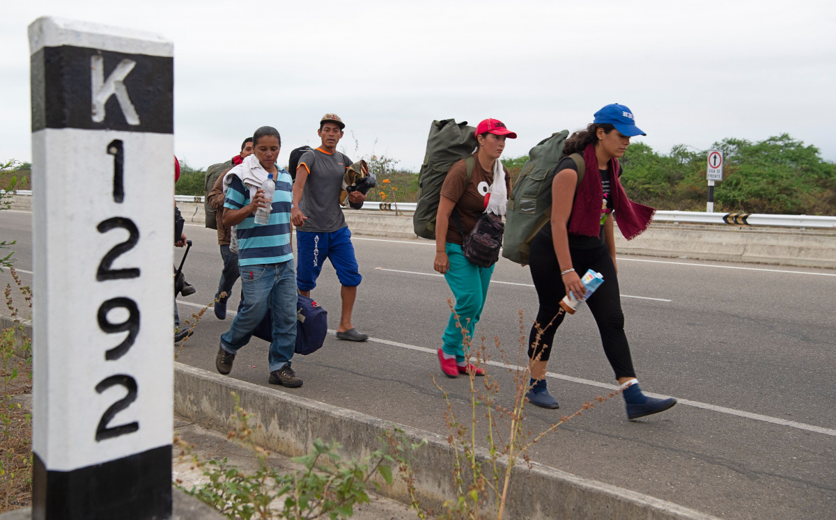 A group of Venezuelan migrants walk southbound along the Pan American highway after receiving their refugee permit. Photo: Getty