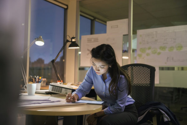 A woman works at her desk in an office late at night.