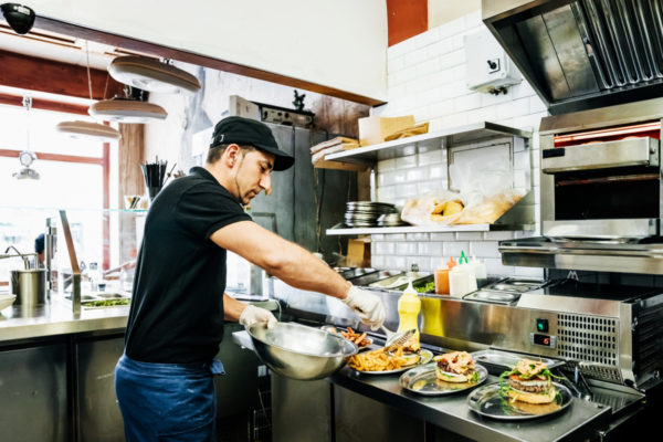 A chef working at a trendy burger bar preparing food for his customers.