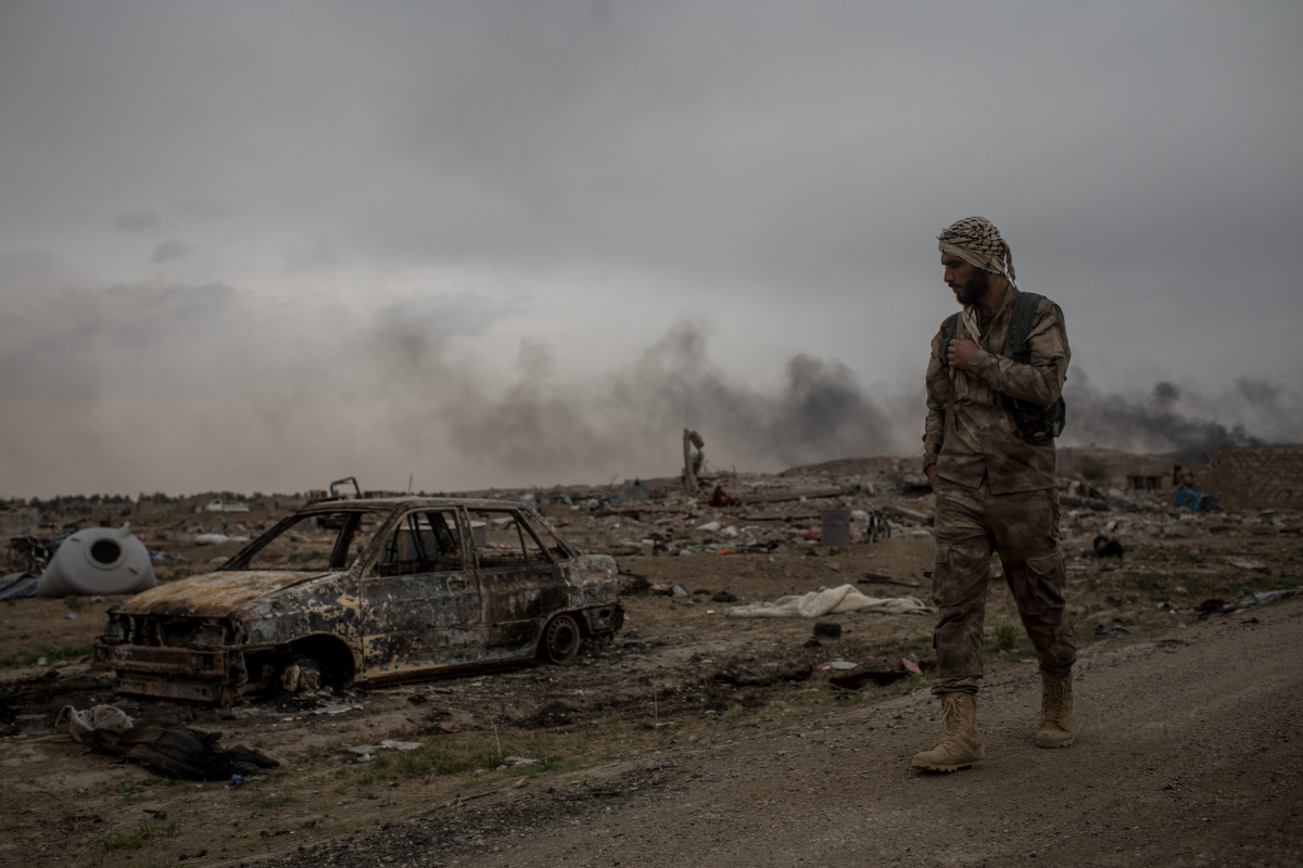A Syrian Democratic Forces Fighter walks past destroyed vehicles in the final ISIL encampment. Photo: Getty