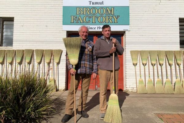 Geoff Wortes and Rob Richards hold brooms in front of the factory.