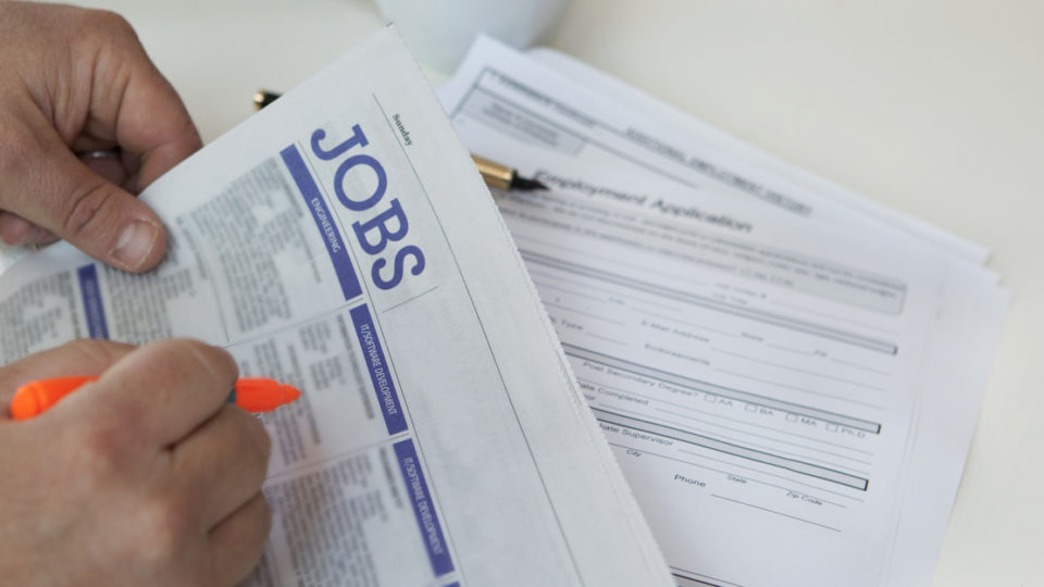 A person searches the paper for a new job.