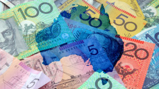 A blue map of Australia superimposed over wads of money.