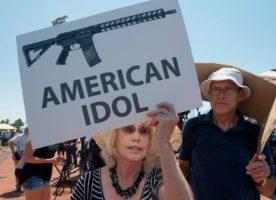 Protestor holds anti-gun sign.