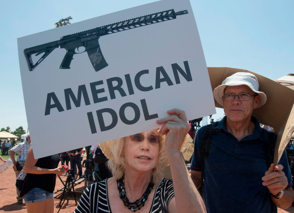 Protestor holds anti-gun sign.