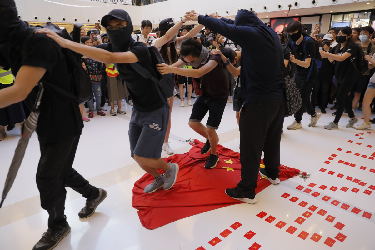A chain of protestors take it in turns to stomp on the Chinese flag.