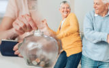 Older couple celebrating while putting money in a jar.