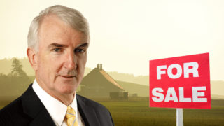 Michael Pascoe standing in front of a farm for sale.