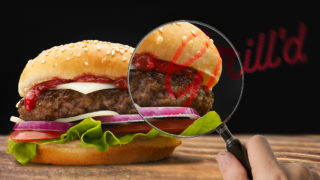 A grill'd burgerbeing investigated by a magnifying glass.