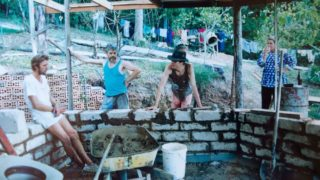 Four Bodhi Farm residents building a structure with cement and bricks