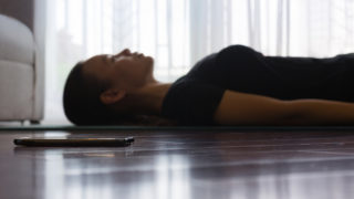 A person trying to relax while listening to guided meditation on her smartphone at home.