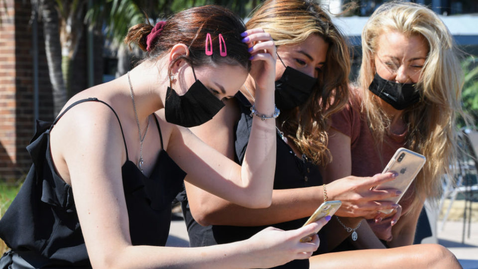 SYDNEY, AUSTRALIA - MARCH 18: Three women wearing face masks use their mobile phones during a work break in Neutral Bay on March 18, 2020 in Sydney, Australia. The Prime Minister Scott Morrison today announced non-essential gatherings of 100 or more people indoors are banned and has declared a human biosecurity emergency. There are now 454 confirmed cases of COVID-19 In Australia - 210 in New South Wales, 94 in Victoria, 78 in Queensland, 32 in South Australia, 31 in Western Australia, seven in Tasmania, three in the Australian Capital Territory and one in the Northern Territory. There have been six confirmed deaths, five in NSW and one in Western Australia. (Photo by James D. Morgan/Getty Images)