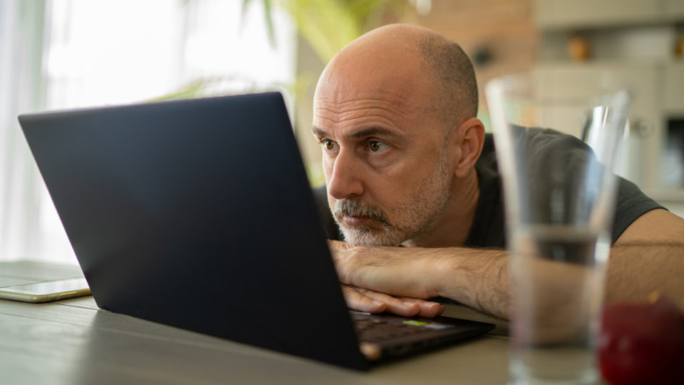 A man looks deflated and stares at his laptop