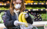 A girl in a mask puts bananas in a plastic bag at the supermarket