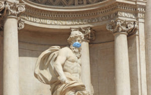 The god Neptune in a mask, in one of the most famous fountains in Rome and in the world, the Trevi Fountain. . Italy is one of the countries hardest hit by the coronavirus pandemic