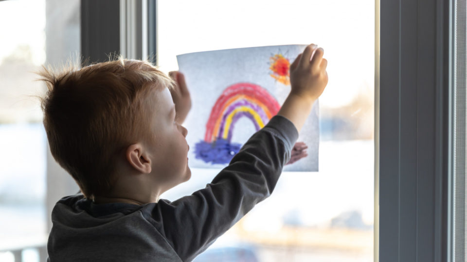 Young Boy sticking his drawing on home window during the Covid-19 crisis - stock photo