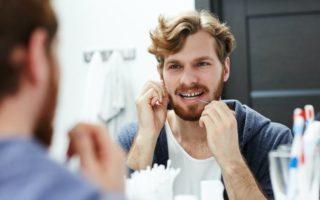 A man flosses his teeth in the bathroom mirror.